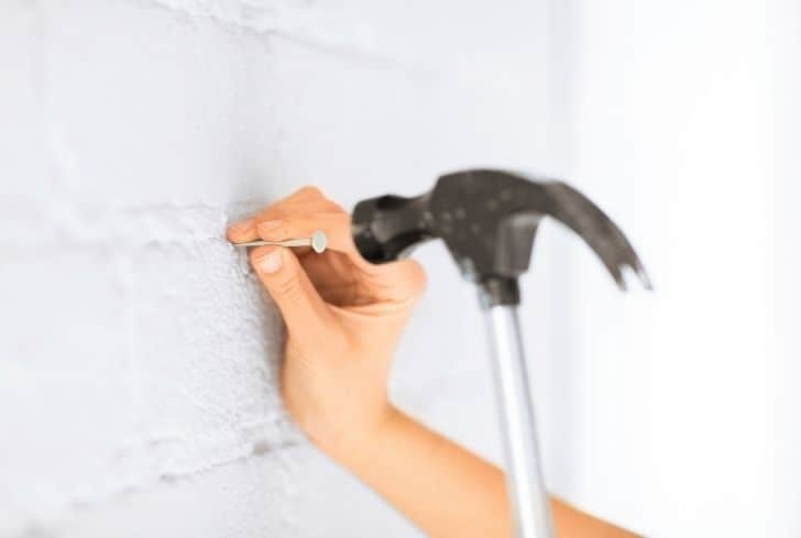hammering-nail-in-wall