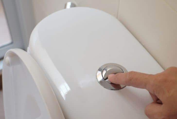 man-pressing-toilet-flush-button